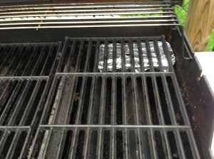Wood chips sitting in disposable foil container directly on flavorizer bars, below the grate. Notice the grate is kinda raised a little (my wood chip container was a little too tall. It all worked out, though. Preheat grill on med-high heat until wood starts to smoke. Then turn off all burners except the one right below the wood. Turn that burner down to low.